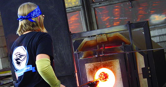 """Photo by Michaela McConnell Senior accounting major Erin Nelson heats her glass pumpkin during the glassblowing demonstration on Friday.""""My favorite part of glass blowing is making something and showing it to people and having them love it and tell me it's pretty,"""" Nelson says."""