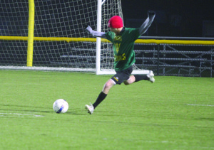 Photo by Hannah Backer  This past week during soccer intramurals, the Swag Devils played the Goal Diggers. Kicking the ball on this rainy, cold night is Zach Davison who is a member of the Swag Devils team.