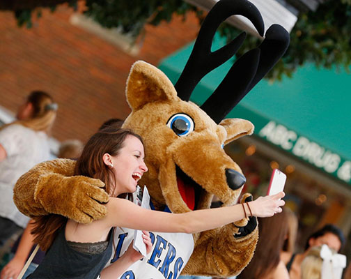 Senior and Sapphire dance team member Meghan Forsgren shows her school pride as she takes a selfie with Louie the Loper.