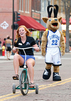 Senior Taylor Kittle embraces her inner child on a tricycle as Louie Loper looks on.