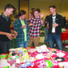 Dallas Doering, Stephanie Paulsen, Drew Thompson, and Austin Partridge stand with their hands up after time runs out in the gingerbread house competition.
