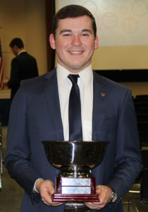 Luke Grossnicklaus, a junior business education major and president of the Sigma Phi Epsilon fraternity shows the Nester Cup given to the fraternity with the highest GPA.