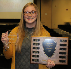 Ivy Prater, president of the Alpha Phi sorority, holds with the award given to the sorority for having the highest GPA among sororities.