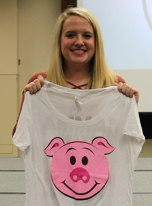 Cady Coy, a senior education major from Norfolk, holds up the shirt she won in the raffle.
