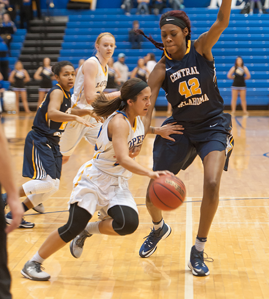 Photos by Todd Rundstrom Senior Alexa Hogberg drives by Central Oklahoma's Jesheon Cooper at the Health and Sports Center on Thursday. Hogberg finished with seven points and three assists to upend the previous top-ranked MIAA Bronchos.