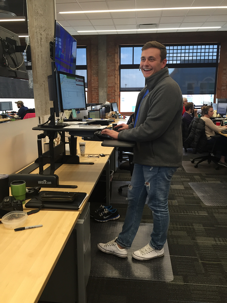 "Jeffrey Olson, a 2015 UNK graduate with a degree in business administration with an emphasis in marketing, at his stand up desk in the GIX office in Grand Island. ""It's a team atmosphere, where we're always pushing towards the same goal – to make GIX the best freight brokerage in the country,"" Olson said."