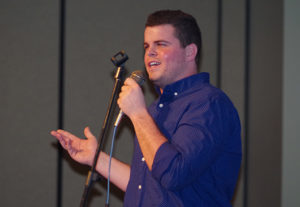 Photo by Sydney Norris Michael McPhillips, senior,  studying middle school education from Humphry, leaves it all on the stage as the crowd's roaring laughter during his stand-up routine.
